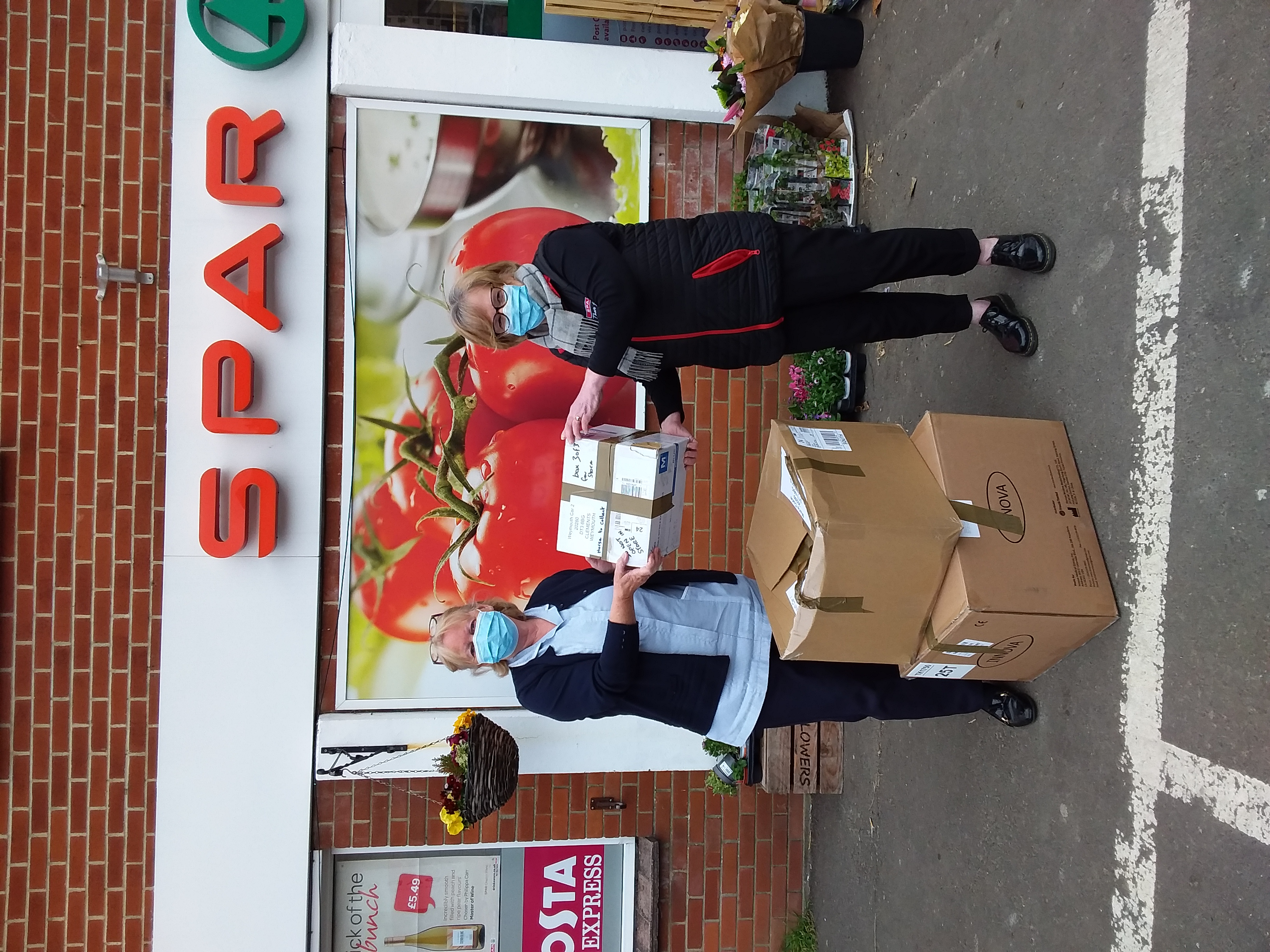 SPAR store owner Barbara Clements hands PPE parcel to Marie Curie Healthcare Assistant Liz Marshal