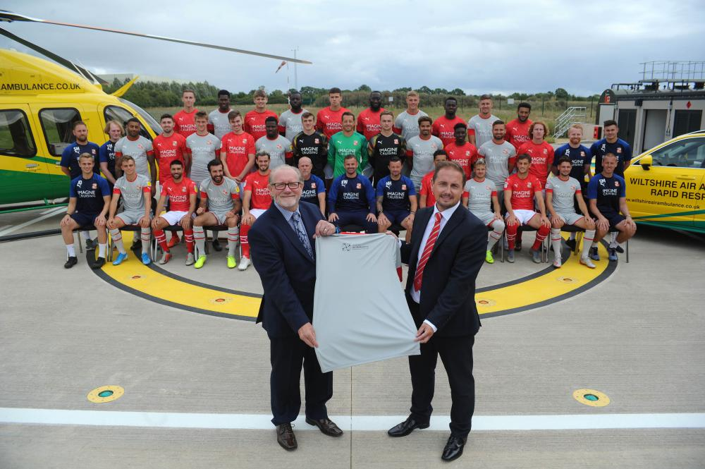 Wiltshire Air Ambulance chief executive David Philpott and Swindon Town chief executive Steve Anderson unveil the away shirt with the charity's logo in front of a team photograph at the airbase.