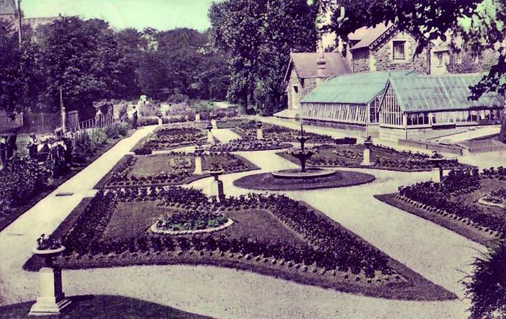 A view of the ornamental bedding scheme with the park keeper's lodge and glass houses in the background  © Swindonstory.uk