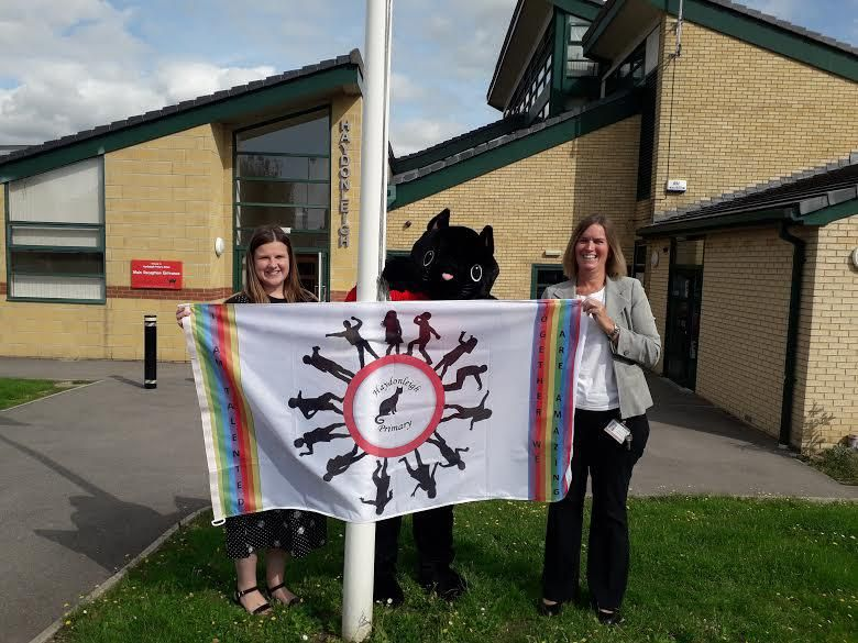 Teacher Kirsty Bragg, left, with head teacher Frances Billinge and the school mascot at the flag-raising ceremony
