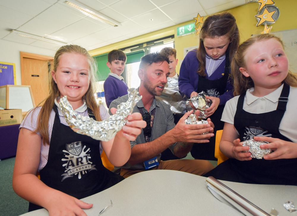The Art Academy founder, Dean McGhee, with students at Oakhurst Primary School