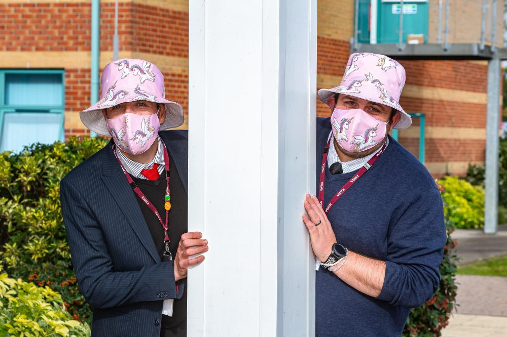Head f Year 11 David Storey and head of Year 7 Joe Randall modelling masks and hats made by the mystery professional seamstress