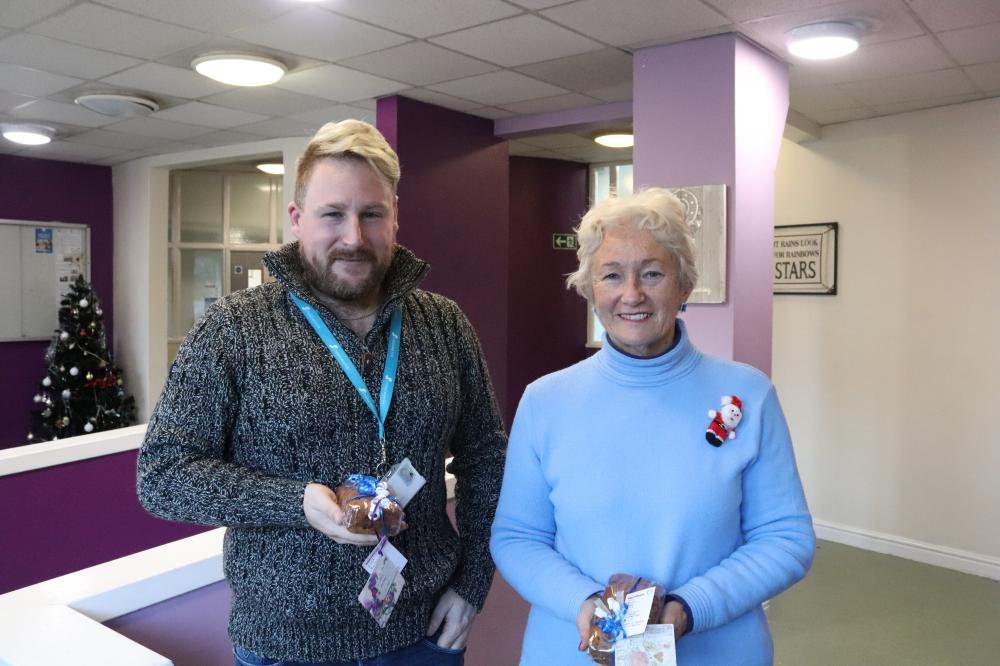 Volunteer Jenny Yallop handing over two homemade cakes to Gareth Hacker for residents at The Foye